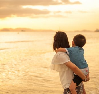 A mother and son on the beach and sea outdoors at sunset with copy space